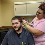 Stylist Dawn putting pink in staff member Devin's hair