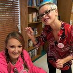 Stylists Lisa Nester is putting pink in Sarah Huffman CNA's hair.